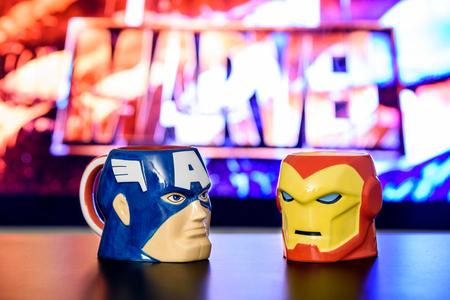 Bucarest, Rumania - 13 de septiembre, 2016: Los aficionados al cine que bebe de Capitán América y Iron Man Tazas En Marvel Avengers noche de película.