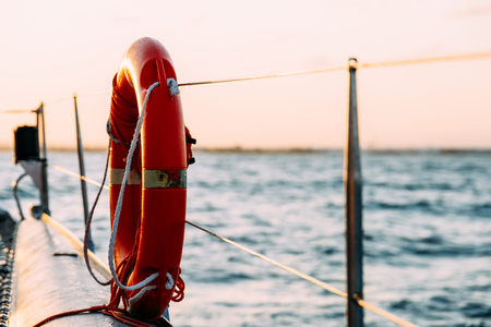 safe water: Red Life Buoy On Cruise Ship Stock Photo