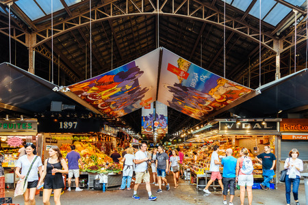 BARCELONA, SPAIN - AUGUST 05, 2016: People In Barcelona Market (Mercat de Sant Josep de la Boqueria), a large public market and a tourist landmark with entrance from La Rambla street.