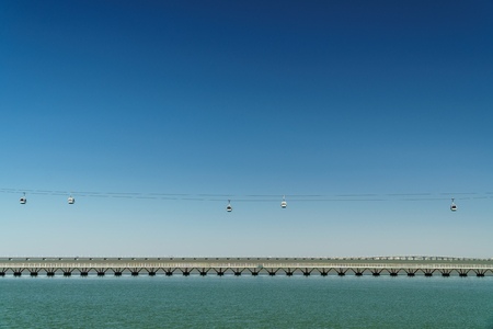 Aerial Cable Cars And Vasco da Gama Bridge In Lisbon, Portugal Stock Photo