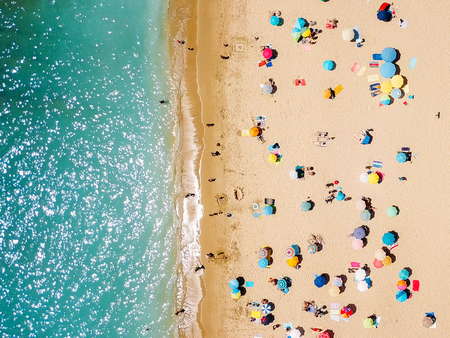 Aerial View From Flying Drone Of People Crowd Relaxing On Beach In Portugal