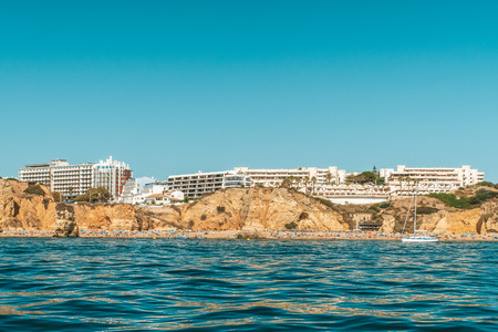 Tourists Having Fun In Water, Relaxing And Sunbathing At Lagos Beach In Algarve, Portugal