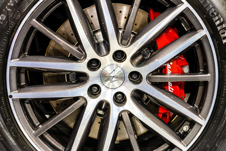 BUCHAREST, ROMANIA - OCTOBER 19, 2018: Maserati Logo Sign Closeup View On Car Alloy Wheel With Red Brake Calipers And Drilled Disk Brake