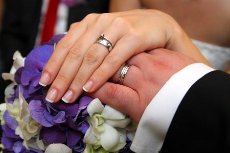 wedding ring hands: bride and groom hands wearing wedding rings over bride bouquet