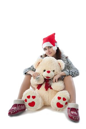girl in a red cap sits with a teddy bear photo