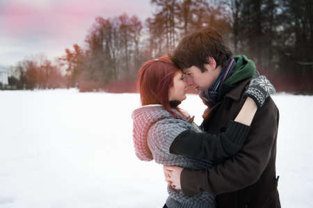 Beautiful young people embracing the winter outdoors  photo
