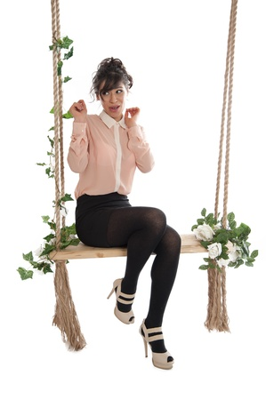 emotional woman: Emotional woman on a swing in the studio isolated background