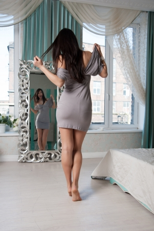 woman in front of a mirror measures a gray dress photo