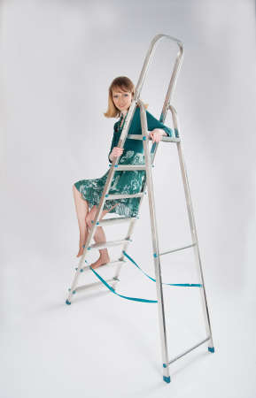 beautiful woman in a green dress sitting on a stepladder Stock Photo