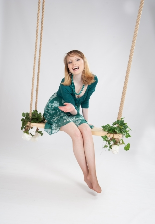 swing seat: beautiful woman in a green dress on a swing