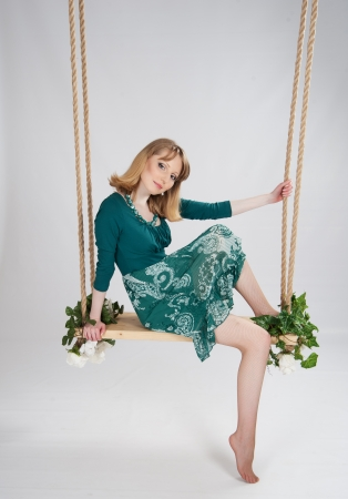 beautiful woman in a green dress on a swing photo