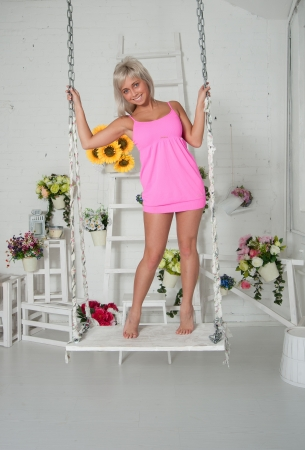 beautiful woman with flowers on a swing in the studio photo