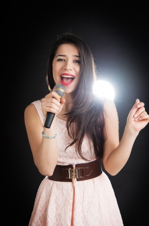 Female singer sings into a microphone on a black background photo