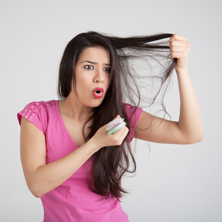 shocked woman losing hair on hairbrush photo