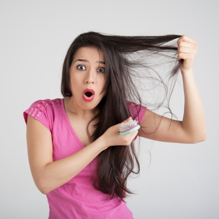 loss: shocked woman losing hair on hairbrush