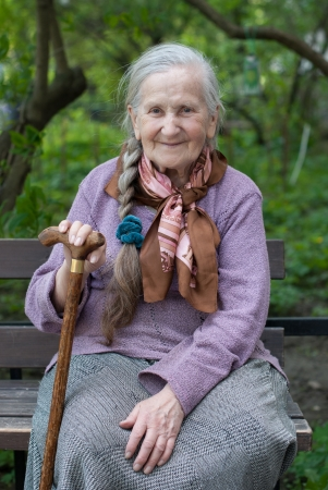 old grandmother with a long braid in the summer in the garden Banque d'images