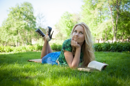 young girl is laying on the grass with a book