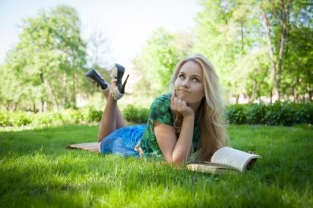 kobiet: młoda dziewczyna leży na trawie z książką Zdjęcie Seryjne