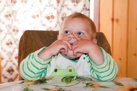 nose picking: little boy picking his nose at the table