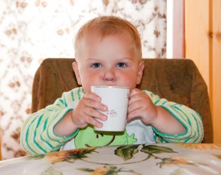 Petit garçon boit à une table dans la cuisine Banque d'images - 21962046