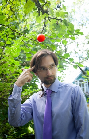 thinking man under the apple in the garden photo