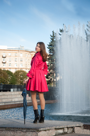 happy young woman in a red raincoat with an umbrella photo