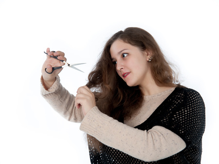 mows: woman mows split ends of hair with scissors