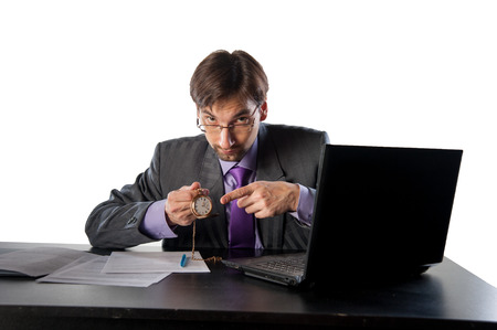 businessman in glasses behind a desk in an office with a clock in his hands photo