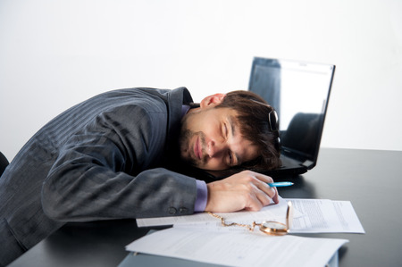 man asleep on a laptop in the workplace photo