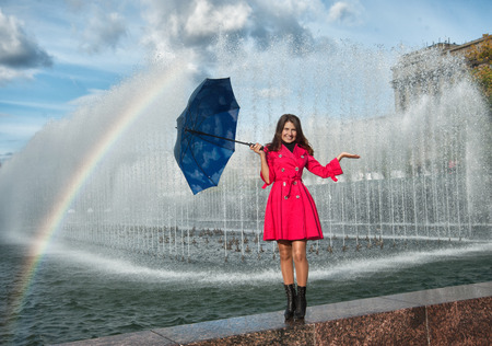 happy woman in red raincoat under the spray and rainbow photo