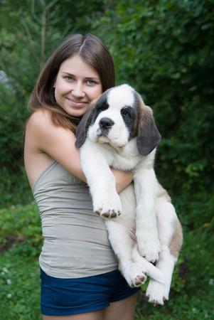st bernard: happy girl holding puppy St. Bernard