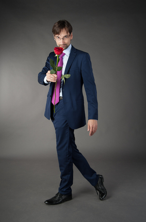 suitor: young mugina in a suit with a rose on the gray . Stock Photo