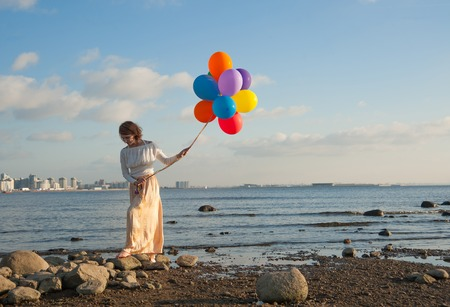 girl with colorful balloons on the rocks on the Bay photo