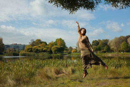Happy woman jumping in a autumn day in the park photo