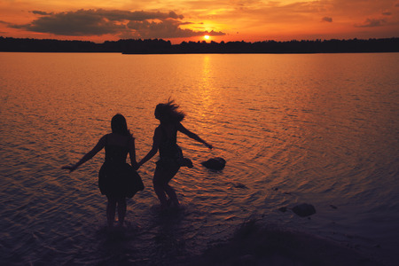 girls jump in the lake at sunset in summer photo