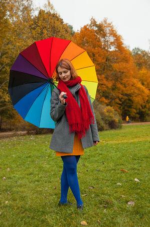 rainbow umbrella: woman in autumn Park with rainbow umbrella
