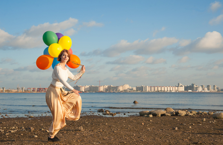 young Jennie jumping on the beach with balloons photo