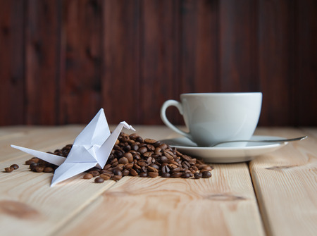 crane origami: Cup of coffee with crane origami on the coffee beans