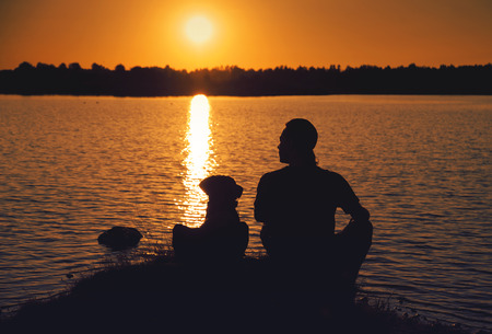 man with a dog walking in the sunset at the lake photo