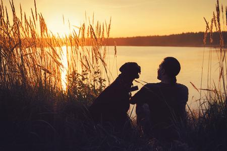 man met een hond lopen in de zonsondergang op het meer Stockfoto