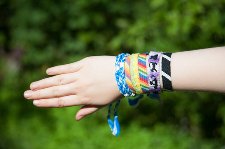many braided bracelets from colored threads on the hand Banque d'images