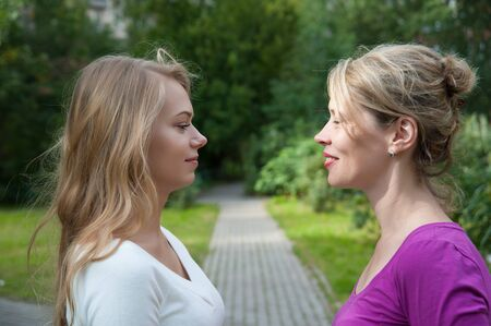 two girlfriends are laughing on the street