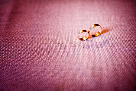 burgundy background: two gold wedding rings on a burgundy background Stock Photo