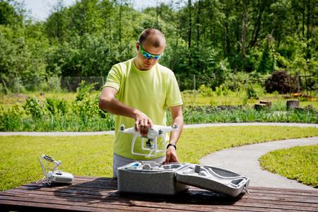 pilot light: Man preparation quadrocopters for flight in the garden