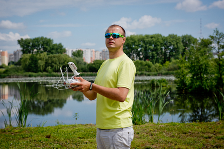 remote controls: young man controls the drone by remote Stock Photo