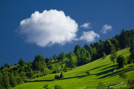White cloud on a blue sky in a green countryside of Romania photo