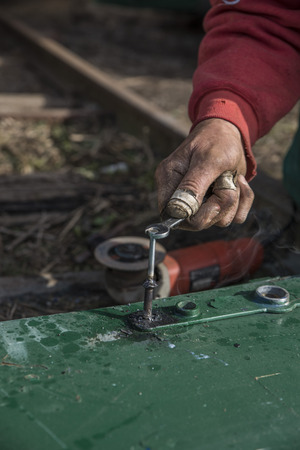 wounded: Wounded welder hands fixing a metal door