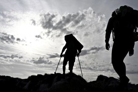 Silhouette of two hikers on a mountain ridge Stock Photo