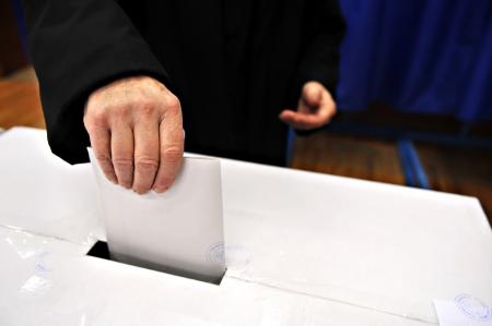 political system: Primer plano de la mano de un hombre poniendo su voto en la urna