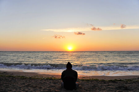 contemplates: A man contemplates the sunrise at the seaside